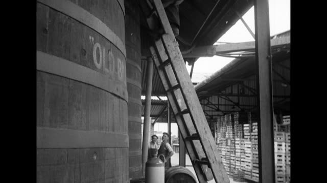 Sequence showing a worker checking a large cider press