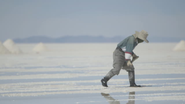 stockvideo's en b-roll-footage met sequence showing a worker wearing a balaclava creating a mound of salt on salt plains, bolivia. - bolivia