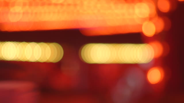 Sequence showing abstract defocused bokeh lights of a fairground waltzer ride as waltzer cars whizz by, UK.