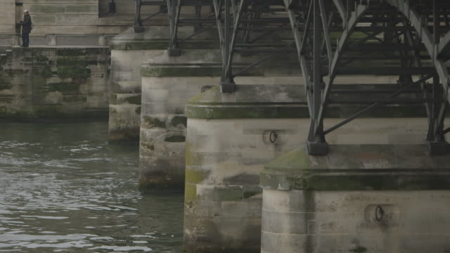 sequence showing abutments underneath the pont des arts, which spans the river seine, in paris, france. - durability stock videos and b-roll footage