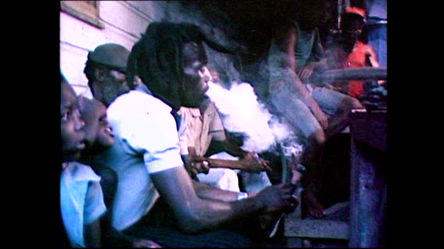 vídeos de stock e filmes b-roll de sequence showing adult jamaican men smoking marijuaa from large pipes. an older man in a red vest smokes indoors before continuing with ironing. cut... - 1981