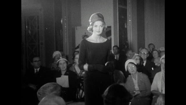 Sequence showing an audience watching a fashion show of women's hats