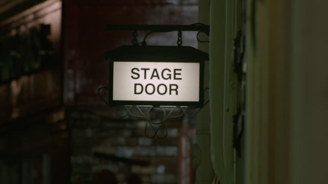 Sequence showing an illuminated sign reading 'STAGE DOOR' outside a London theatre, UK.