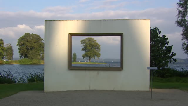 Sequence showing an outdoor sculpture framing a view of Lake Schwerin at Schwerin Castle Germany NNBZ126J ABSA627D
