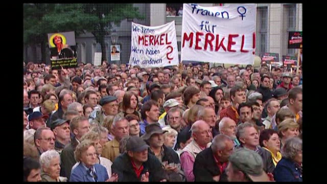 sequence showing angela merkel speaking at an outdoor election rally in germany; 2005. political sign in crowds. angela merkel speaking at lectern.... - 2005 stock-videos und b-roll-filmmaterial