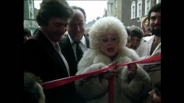sequence showing barbara windsor cutting the ribbon to open a supermarket in stoke newington, uk alongside her husband, ronnie knight; 1981. - smiling stock videos & royalty-free footage