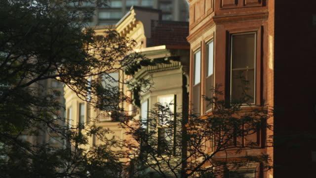 vídeos de stock, filmes e b-roll de sequence showing bay-windowed buildings lit up in evening sunlight, boston, massachusetts. - janela saliente