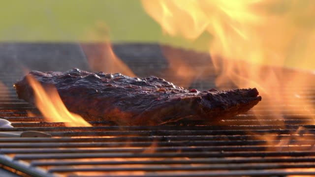 sequence showing beef steaks cooking on a barbecue, uk. - flame stock videos & royalty-free footage