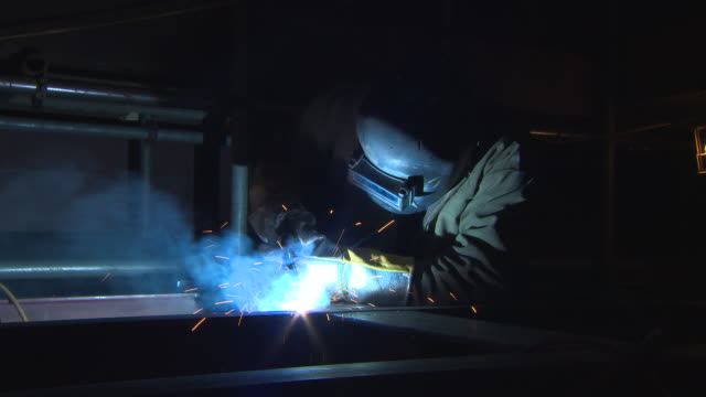 sequence showing blue light illuminating a welder in protective gear suddenly going out at a shipyard in glasgow, scotland. - welding stock videos & royalty-free footage