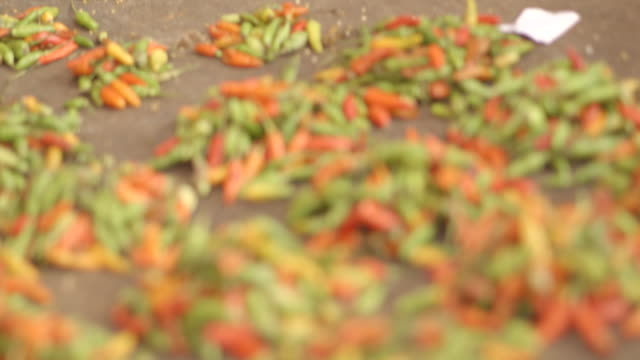 POV sequence showing brightly-coloured chillies on market stalls in Kenema, Sierra Leone.