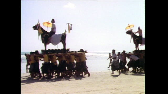 sequence showing bullshaped 'bade' sarcophagi being carried and followed onto beach by a crowd of people as part of a traditional hindu funeral... - pacific islander stock videos & royalty-free footage