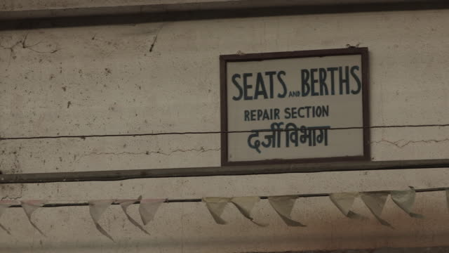 Sequence showing bunting waving next to a sign denoting the seats and berths repair section of a maintenance workshop Mumbai Maharashtra India...