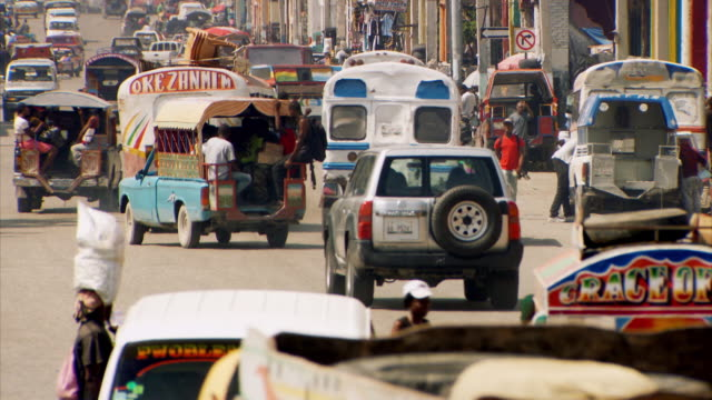 stockvideo's en b-roll-footage met sequence showing buses, tap taps, cars and people going about their everyday lives on the streets of port-au-prince, haiti. - haïti