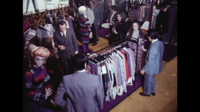 Sequence showing buyers browsing rails of clothes at a fashion event in London