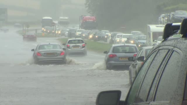 vídeos de stock, filmes e b-roll de sequence showing cars driving through heavy rain and flooded roads in belfast - chuva congelada
