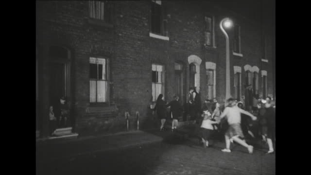 Sequence showing children playing 'ring a ring of roses' on a terraced street