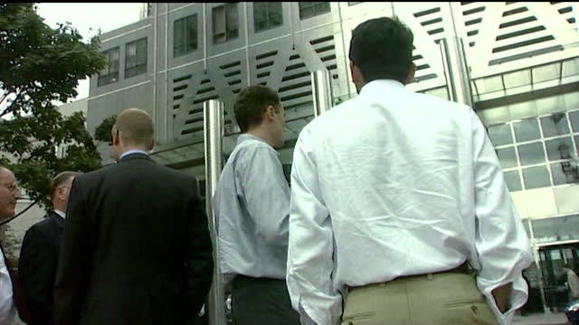 sequence showing city workers in canary wharf being evacuated on september 11th 2001. exterior of canary wharf. to male city workers waiting outside.... - information sign stock videos & royalty-free footage