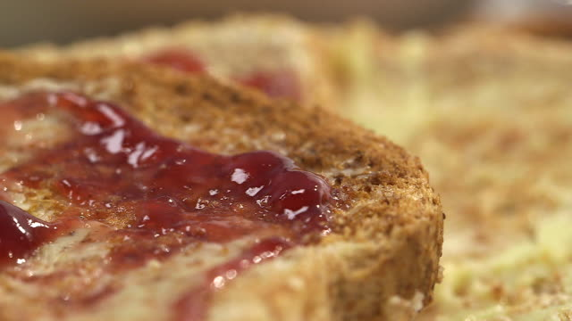 sequence showing close-ups of a breakfast of buttered toast with jam and a bowl of cornflakes. - preserve stock videos and b-roll footage