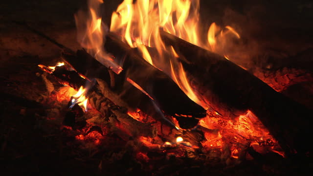 sequence showing close-ups of a campfire burning to embers in front of a snow cave, yukon, canada. - lagerfeuer stock-videos und b-roll-filmmaterial