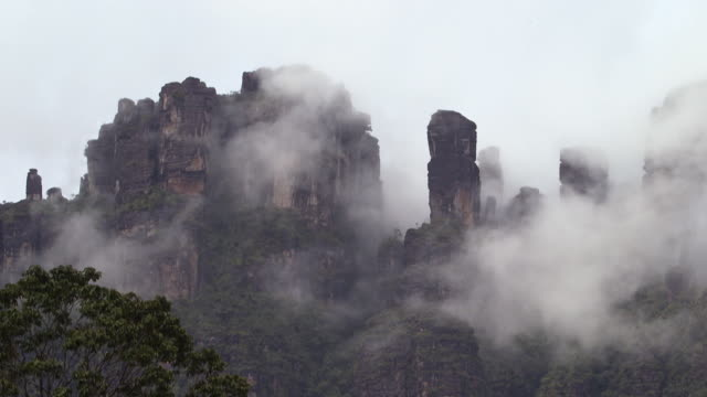 Sequence showing cloud rolling around ancient, exposed cave structures at the top of a Tepui mountain, Venezuela.