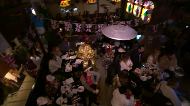 vídeos de stock, filmes e b-roll de sequence showing crowds enjoying the royal wedding of prince harry and meghan markle in a bar in los angeles - ambiente evento