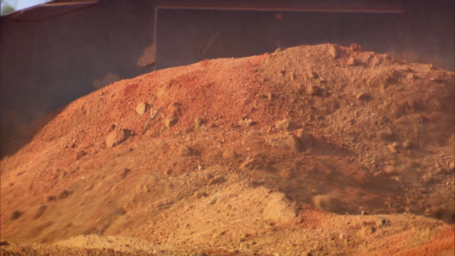 Sequence showing diggers excavating earth at the Rio Tinto Alcan bauxite mine near Weipa.