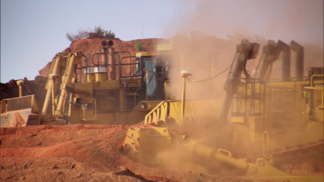 sequence showing diggers excavating earth at the rio tinto alcan bauxite mine near weipa. - mining stock videos & royalty-free footage