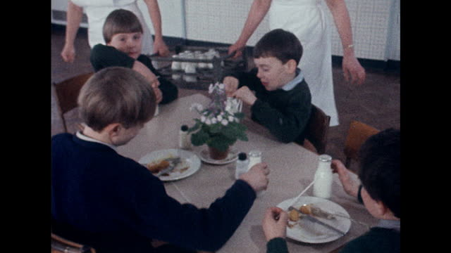 sequence showing dinner ladies handing out bottles of milk to school children during their lunch break - 1970 stock videos & royalty-free footage