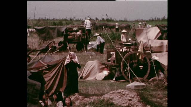 sequence showing displaced my thanh village refugees settling in a makeshift camp along the side of a road while armed forces defend the village;... - non us film location stock videos & royalty-free footage