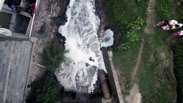 vídeos de stock, filmes e b-roll de sequence showing dramatic aerial views of a community where textiles factories are reported to be polluting the river citarum, indonesia. - tintura