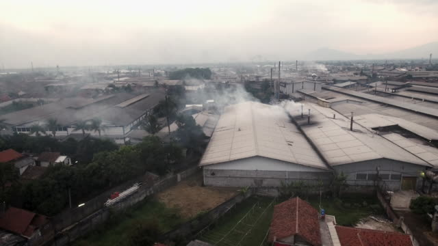 sequence showing dramatic aerial views of factories in an area where the textiles industry is reported to be severely polluting the river citarum, indonesia. - toxic waste stock videos & royalty-free footage