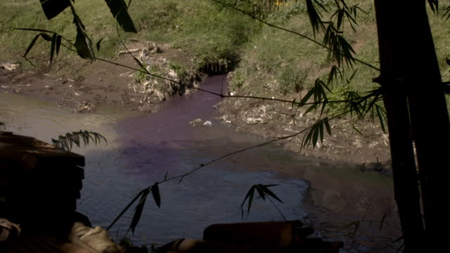 sequence showing dye reportedly from textiles factories being leaked into the river citarum causing water pollution, indonesia. - textile industry stock videos & royalty-free footage
