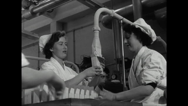 sequence showing factory workers filling cartons with ice cream at the wall's dairy factory - cibi surgelati video stock e b–roll