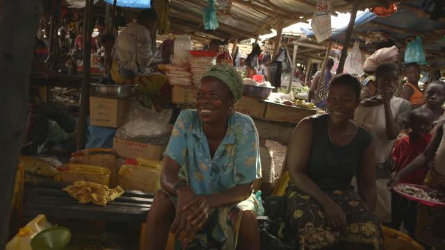 Sequence showing female stallholders at a busy market in Kenema, Sierra Leone.