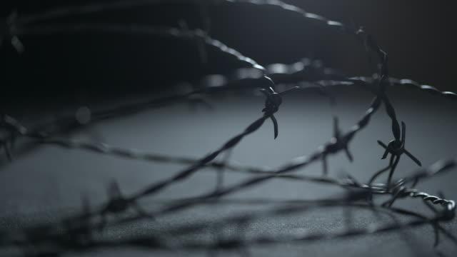 vídeos de stock, filmes e b-roll de sequence showing focus pulls over looped barbed wire in a dark studio. - encurralado