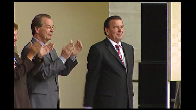 sequence showing gerhard schröder attending a political election rally in germany; 2005. walking through crowds waving. large audience seated and... - hand raised stock videos & royalty-free footage