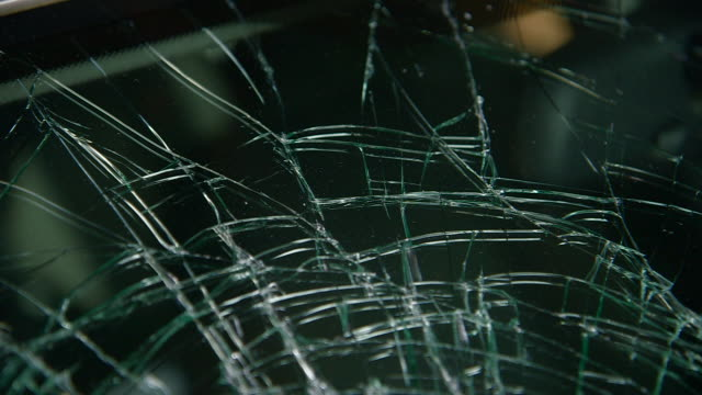 sequence showing handheld close-ups of the shattered safety glass of a car windscreen, uk. - road accident stock videos & royalty-free footage
