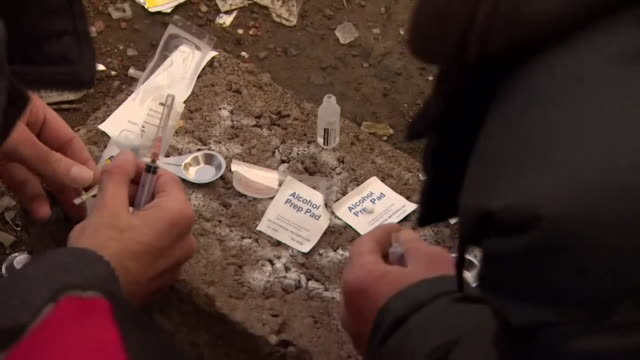 stockvideo's en b-roll-footage met sequence showing heroin users preparing needles for injection in glasgow scotland - injecting heroin