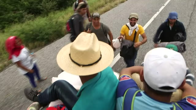 sequence showing honduran 'caravan' migrants boarding a flat bed truck heading toward oaxaca mexico - 隊列点の映像素材/bロール