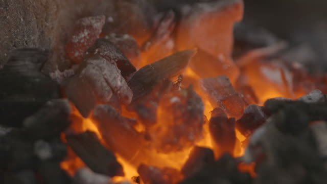 sequence showing hot coals and fire coming into and going out of focus at a workshop in sierra leone. - coal stock videos & royalty-free footage