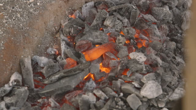 sequence showing hot coals at a workshop in sierra leone. - scraping stock videos and b-roll footage