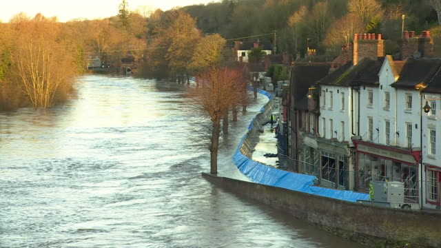sequence showing how the increase of water in the river severn in ironbridge, shropshire, moved the flood barrier - ironbridge shropshire stock videos & royalty-free footage