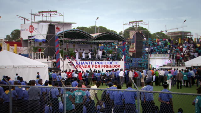 vidéos et rushes de sequence showing hundreds of people sitting in the stands of a stadium watching a charity concert held by the restavek freedom foundation to raise awareness of the plight of enslaved children in haiti. - services sociaux