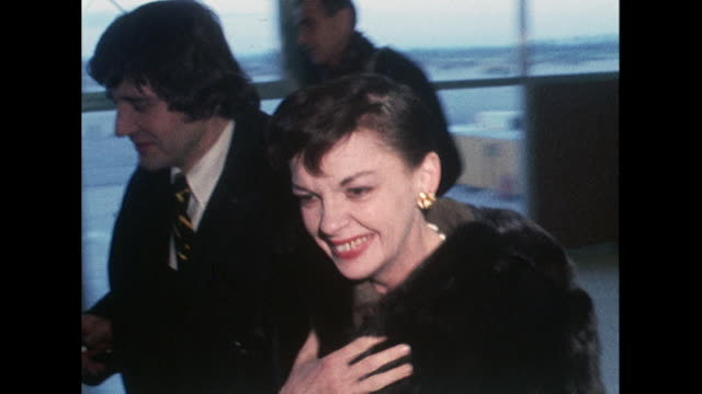 Sequence showing Judy Garland arriving at London Airport and being handed a writ to stop her performing in an upcoming show