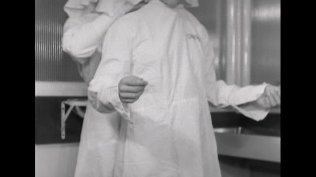 sequence showing laboratory workers putting on their safety gear - arbeitssicherheit stock-videos und b-roll-filmmaterial