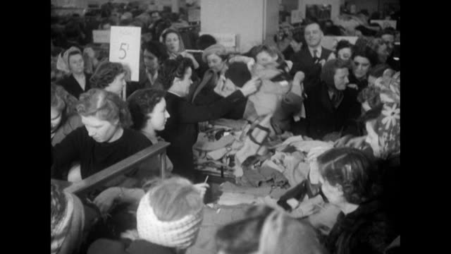 Sequence showing large crowds browsing January sales goods in a department store