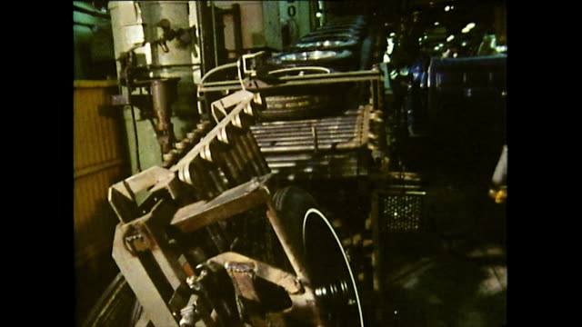 sequence showing large tyres being delivered to the production line via a belt conveyor roller. worker fits wheel nuts by hand and secures with... - detroit michigan stock videos & royalty-free footage