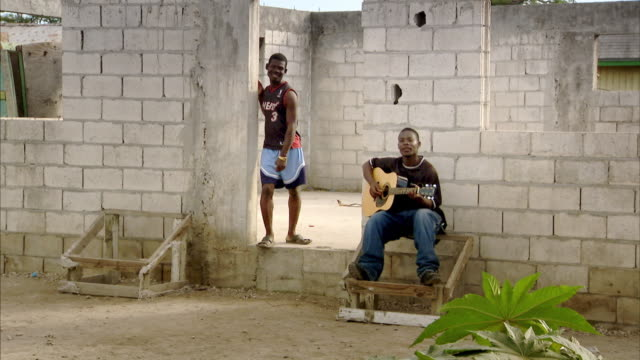 vídeos de stock e filmes b-roll de sequence showing life for people living in a slum in the bahamas. - vender