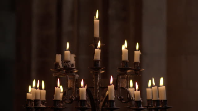 Sequence showing lit, flickering candles on a candelabra in a church, UK.