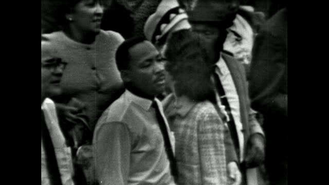 vídeos de stock, filmes e b-roll de sequence showing martin luther king leading a large group of marchers through montgomery, alabama to the state capitol building; 25th march 1965.... - 1965